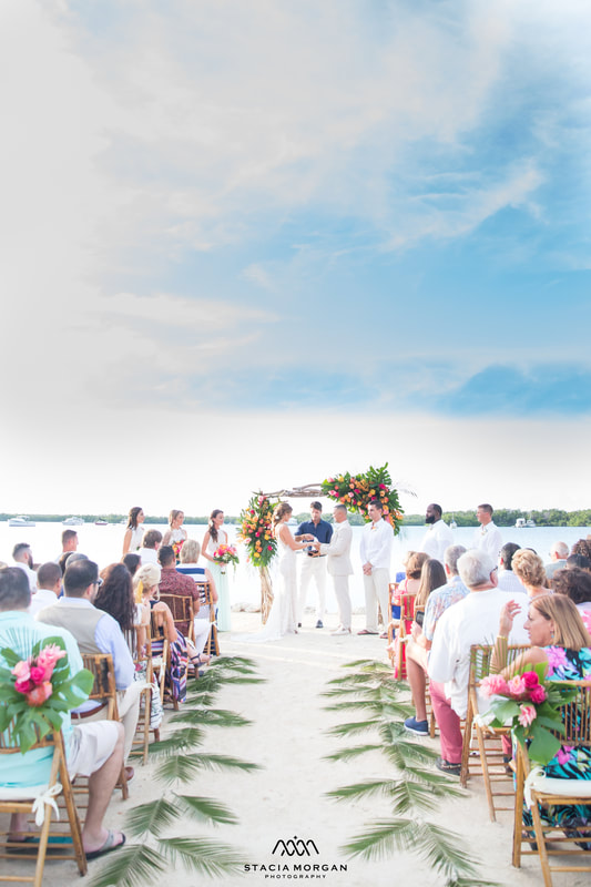 South Florida wedding, bright flowers on arch and green palms along aisle